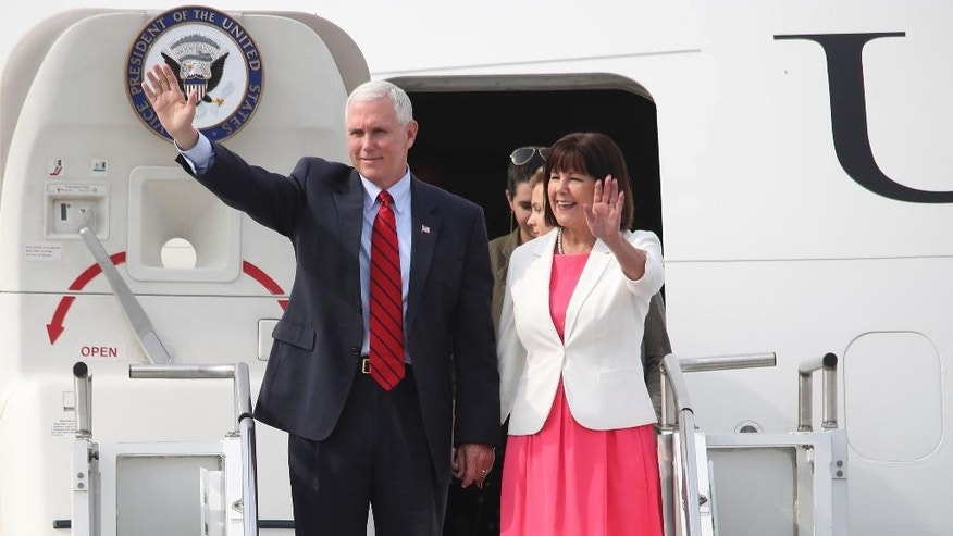 U.S. Vice President Mike Pence and his wife Karen wave upon their arrival at Osan Air Base in Pyeongtaek, South Korea, Sunday, April 16, 2017. Pence arrived in South Korea on Sunday to begin a 10-day trip to Asia that comes amid turmoil on the Korean Peninsula over North Korea's threats to advance its nuclear and defense capabilities, and just after a failed missile launch by the North. (Kim Do-hoon/Yonhap via AP)