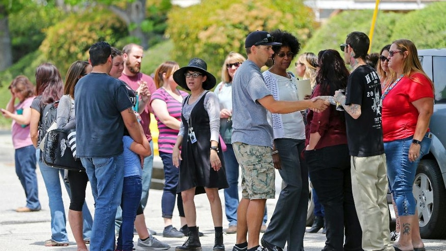 In this Tuesday, April 11, 2017 photo, North Park Elementary School principal Yadira Downing, center right facing camera, with glasses on, talks with faculty, staff and parents following the shooting death of a teacher and a student on Monday at the school in San Bernardino, Calif. Classes are scheduled to resume Monday, April 17, with additional personnel and crisis counselors on hand to help students who may need support. The school will also have enhanced security procedures. (AP Photo/Reed Saxon)