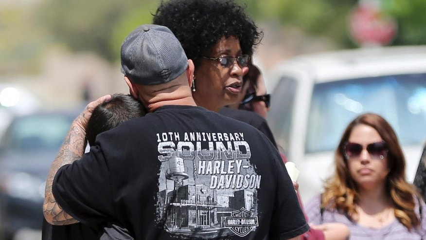 In this Tuesday, April 11, 2017 photo, North Park Elementary School principal Yadira Downing, center rear, talks with Ruben Gutierrez and his grandson Jeffrey Imbriani, 7, after shooting death of a teacher and a student on Monday at the school in San Bernardino, Calif. Imbriani said he was a friend of Jonathan Martinez, the student who died. Classes are scheduled to resume Monday, April 17, with additional personnel and crisis counselors on hand to help students who may need support. The school will also have enhanced security procedures. (AP Photo/Reed Saxon)