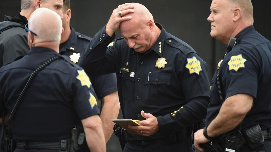"Fresno Police chief Jerry Dyer reviews notes on the triple fatal shooting before addressing the media Tuesday, April 18, 2017, in Fresno, Calif. A man shot and killed three people on the streets of downtown Fresno on Tuesday, shouting ""God is great"" in Arabic during at least one of the slayings and later telling police that he hates white people, authorities said. Kori Ali Muhammad, 39, was arrested shortly after the rampage, whose victims were all white, police said. He also was wanted in connection with another killing days earlier, in which a security guard was gunned down at a Fresno motel after responding to a disturbance. (John Walker/Fresno Bee via AP)"