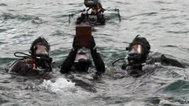 In this Saturday, April 15, 2017 photo released by Pacific Historic Parks, divers take the urn containing the remains of Raymond Haerry underwater to his final resting place within the sunken hull of the USS Arizona during a ceremony at the USS Arizona Memorial in Honolulu. Haerry, who died in September in Rhode Island, was one of the last surviving veterans of the sinking of the Arizona during the attack on Pearl Harbor in World War II. (Elaine Simon/Pacific Historic Parks via AP)
