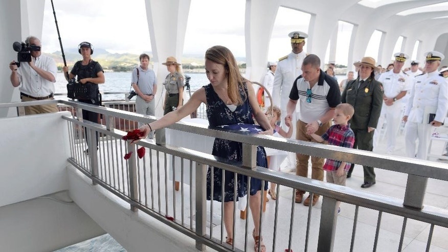 In this Saturday, April 15, 2017 photo released by Pacific Historic Parks, Jessica Marino, granddaughter of Raymond Haerry, drops rose petals into the water at the USS Arizona Memorial in Honolulu.