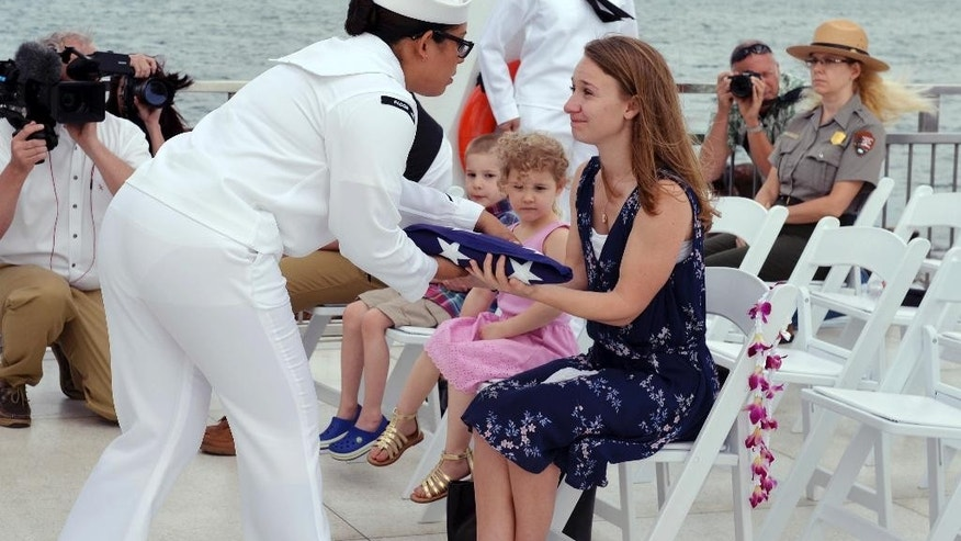 In this Saturday, April 15, 2017 photo released by Pacific Historic Parks, Jessica Marino, center, granddaughter of Raymond Haerry, receives the U.S. flag from the U.S. Navy during a ceremony at the USS Arizona Memorial in Honolulu.