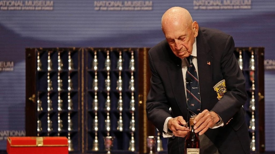 "FILE – In this Nov. 9, 2013, file photo, retired U.S. Air Force Lt. Col. Richard ""Dick"" Cole, a surviving member of the 1942 raid on Tokyo led by Lt. Col. Jimmy Doolittle, opens an 1896 bottle of cognac the Raiders had been saving for their final toast, at the National Museum of the U.S. Air Force at Wright-Patterson Air Force Base in Dayton, Ohio. Cole, co-pilot of the Doolittle Tokyo Raiders' lead plane and a fly-over by vintage B-25 bombers will be part of Ohio events April 17-18, 2017 for the 75th anniversary of the daring attack that helped turn the tide of World War II. (AP Photo/Al Behrman, File)"
