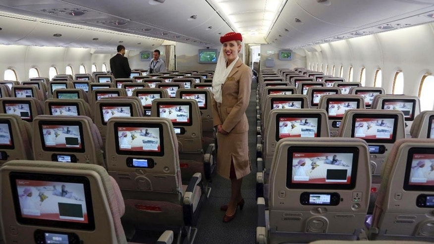 FILE- In this Wednesday, March 12, 2014 file photo, a stewardess stands inside an Emirates A380 aircraft, the world's largest passenger airline, during the fourth Indian Aviation show at Begumpet airport in Hyderabad, India. The Middle East's biggest airline says it is reducing flights to the United States because of a drop in demand caused by tougher U.S. security measures and attempts by the Trump administration to ban travelers from a number of Muslim-majority nations. (AP Photo/Mahesh Kumar A., File)