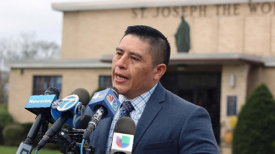 Joselo Lucero speaks to reporters before the funeral of Justin Llivicura at St. Joseph the Worker Church in East Patchogue, N.Y., on Wednesday, April 19, 2017. Lucero's brother, Marcelo Lucero, was killed in 2008 in nearby Patchogue, by a group of young men who admitted they routinely attacked Hispanic victims. He said Wednesday he was attending the funeral to lend support to the family of Llivicura, who was among four young men found dead in a park in Central Islip, N.Y., on Wednesday, April 12, 2017. Police suspect the deaths of Llivicura and three others may have been at the hands of the MS-13 street gang. (AP Photo/Frank Eltman)