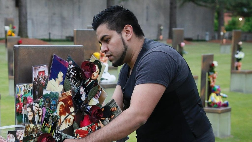 Brian Martinez, 31, attaches a wreath made of family photos to his father's chair in the Field of Chairs at the Oklahoma City Memorial in Oklahoma City, Wednesday, April 19, 2017, the 22nd anniversary of the Oklahoma City bombing, which killed is father, Rev. Gilbert X. Martinez.Survivors and family members of those killed in the Oklahoma City bombing will gather for a remembrance service Wednesday, the 22nd anniversary of the attack. Carson is speaking at the 22nd Anniversary Remembrance Ceremony. (AP Photo/Sue Ogrocki)