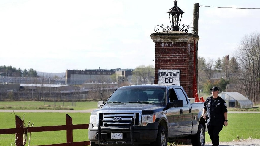 A policeman guards an entrance to the Souza-Baranowski Correctional Center, Wednesday, April 19, 2017, in Shirley, Mass. Former NFL star Aaron Hernandez, who was serving a life sentence for a murder conviction and just days ago was acquitted of a double murder, died after hanging himself at the prison early Wednesday, Massachusetts prisons officials said. (AP Photo/Elise Amendola)