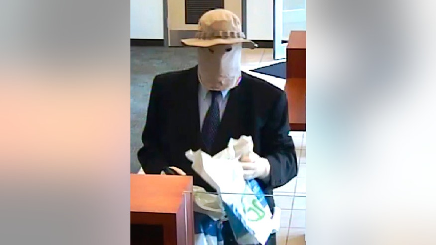 "This image made from a surveillance video provided by the FBI shows a disguised suspect robbing a PNC Bank on July 2, 2016, in North Wales, Pa. The FBI has arrested a suburban Philadelphia man it says was the ""Straw Hat Bandit,"" a bank robber who wore a straw hat, mask and other disguises in stickups dating back to 2012. A federal indictment returned Wednesday, April 19, 2017, charged Richard Boyle, already a convicted bank robber, with carrying out 11 bank robberies that netted him nearly a half-million dollars. (FBI via AP)"