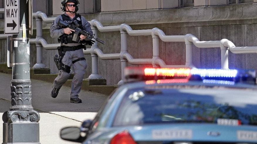 A police officer carrying a rifle runs past a downtown building and near the scene of a shooting involving several police officers in downtown Seattle, Thursday, April 20, 2017. (AP Photo/Elaine Thompson)