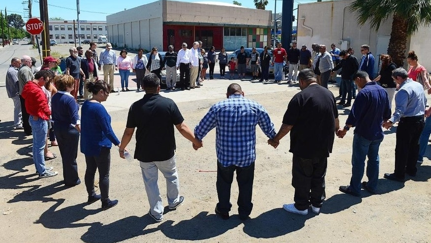 Pastors and church leaders gather for a final prayer following a prayer walk for the victims of Tuesday's triple-homicide near downtown Fresno, Calif., Thursday, April 20, 2017. Members of the Pastor Clusters of the Fresno/Clovis area traced the route of the alleged killer, holding prayers at the location of each victim. (Craig Kohlruss/The Fresno Bee via AP)
