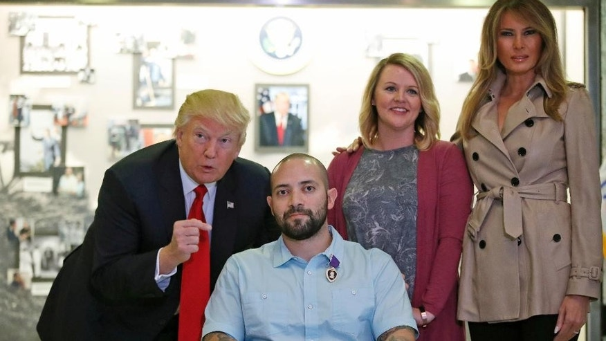 President Donald Trump, left, points after awarding a Purple Heart to U.S. Army Sgt. First Class Alvaro Barrientos, with first lady Melania Trump, right, and Tammy Barrientos, second from right, at Walter Reed National Military Medical Center, Saturday, April 22, 2017, in Bethesda, Md. (AP Photo/Alex Brandon)