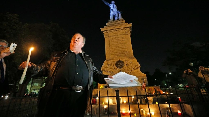 Charles Lincoln speaks during a candlelight vigil at the statue of Jefferson Davis in New Orleans, Monday, April 24, 2017. New Orleans will begin taking down Confederate statutes, becoming the latest Southern body to divorce itself from what some say are symbols of racism and intolerance. (AP Photo/Gerald Herbert)