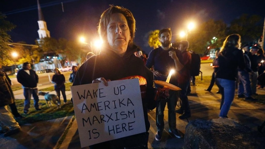 Dana Farley, of New Orleans, participates in a candlelight vigil at the statue of Jefferson Davis in New Orleans, Monday, April 24, 2017. New Orleans will begin taking down Confederate statutes, becoming the latest Southern body to divorce itself from what some say are symbols of racism and intolerance. (AP Photo/Gerald Herbert)