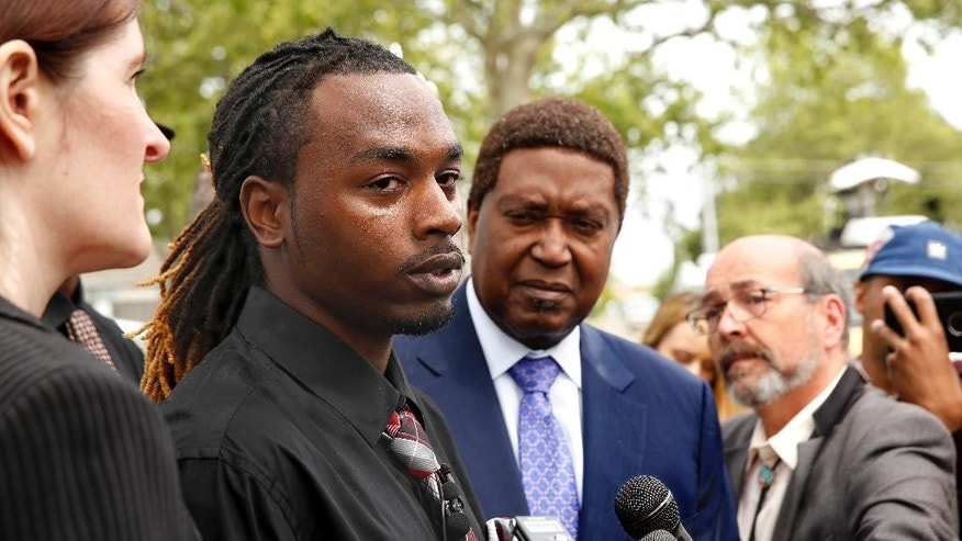 Nandi Cain, left, discusses the alleged beating he received from a Sacramento Police officer two weeks ago during a news conference Monday, April 24, 2017, in Sacramento, Calif. Cain's attorney, John Burris, right, announced that a federal civil rights lawsuit has been filed against the city and county of Sacramento for allegations that Cain was beaten by Sacramento Police Officer Anthony Figueroa, who had stopped Cain for jaywalking. (AP Photo/Rich Pedroncelli)
