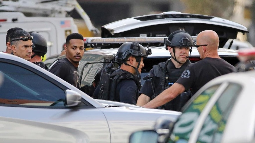 Los Angeles SWAT officers take a man, second from left, into custody after an hours-long search of a building in Los Angeles' downtown Garment District, Monday, April 24, 2017. Police say they were called to the corner of 8th and Santee Streets shortly before noon, when officers responded to a call about gunshots fired in the area. The man was tracked to a nearby building, triggering a room-by-room search of the entire structure before he called police and surrendered without incident. (AP Photo/Reed Saxon)