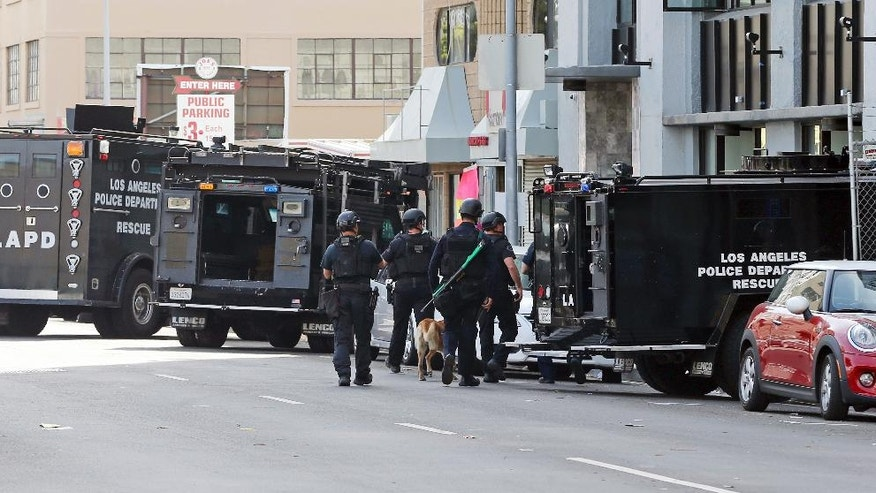 Los Angeles police officers and a search dog prepare to enter a building, right, in Los Angeles' downtown Garment District Monday, April 24, 2017. Police converged on the apartment building Monday as they searched for a man who they believe shot at a passing motorist before running inside the building. (AP Photo/Reed Saxon)
