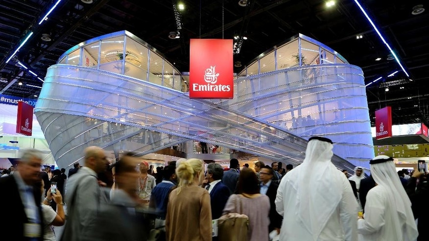 "People visit the Emirates stand during the Arabian Travel Market Exhibition in Dubai, United Arab Emirates, Tuesday, April 25, 2017. The chairman and CEO of Dubai's long-haul carrier Emirates says he ""can't dig into somebody's mind"" to understand why the U.S. instituted a ban on laptops and other personal electronics in carry-on luggage from 10 cities in Muslim-majority countries. (AP Photo/Kamran Jebreili)"