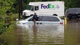 Jamesha Merritt exits a flooded vehicle in Raleigh, N.C., Tuesday, April 25, 2017. Storms have dumped several inches of rain on North Carolina's capital, prompting firefighters to rescue people from their vehicles and delaying school bus schedules. (AP Photo/Gerry Broome)