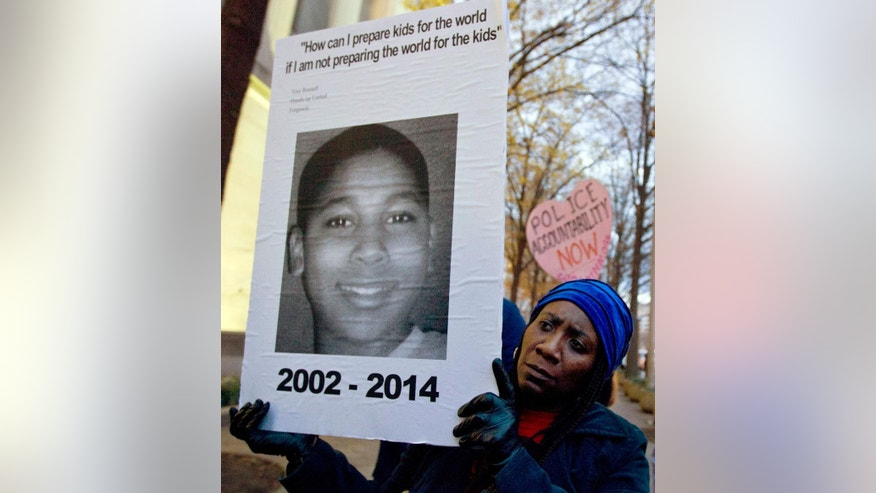 FILE - In this Dec. 1, 2014, file photo, Tomiko Shine holds up a picture of Tamir Rice, the 12 year old boy fatally shot by a rookie police officer in Cleveland, Ohio, on Nov. 22, during a protest in Washington, D.C. Cleveland.com reported newly public recorded police interviews with Officers Frank Garmback and Timothy Loehmann were done within days of the November 2014 death of Rice, who'd been playing with a pellet gun. (AP Photo/Jose Luis Magana, File)