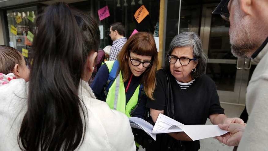 In this Tuesday, April 11, 2017, photo, Sarah Gozalo, center left, and Marisa Lohse, center right, of the New Sanctuary Coalition of NYC, review the Application for Asylum of Joselin Marroquin-Torres, left, before her appearance in federal immigration court in New York.
