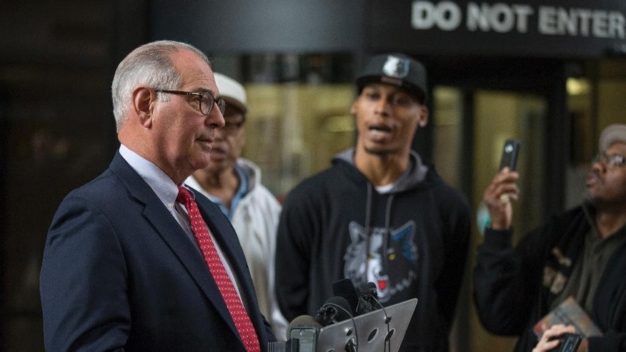Hennepin county attorney Mike Freeman, left, was interrupted Wednesday April 26, 2017, by Cameron Clark, center, who disagreed with the 15 years sentencing that Allen Scarsella received for shooting him and 4 other men in Minneapolis, Minn. (Jerry Holt /Star Tribune via AP)