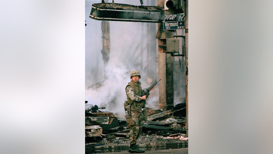 FILE - In this Los Angeles, April 30, 1992 file photo, a National Guardsman stands next to a burned out business area at Vermont Avenue and Wilshire Boulevard during the second day of rioting in the city. (AP Photo/David Longstreath)