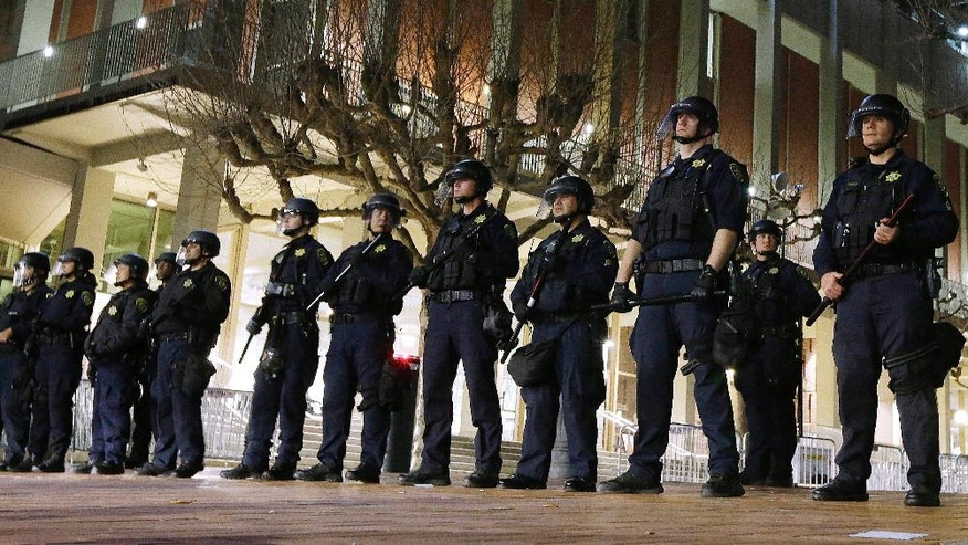 FILE - In this Feb. 1, 2017, file photo, University of California, Berkeley police guard the building where Breitbart News editor Milo Yiannopoulos was to speak in Berkeley, Calif. UC Berkeley police took a hands-off approach to protesters on the campus when violent rioters overtook a largely peaceful protest against a controversial speaker. After a series of protests around the country, some institutions are rethinking their security and tactics in an age of growing political polarization. (AP Photo/Ben Margot, File)