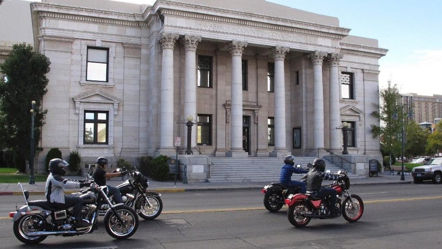 FILE - In this Sept. 23, 2016, file photo, motorcyclists drive pass in front of the Washoe County Courthouse downtown Reno, Nev. marking the fifth anniversary of a deadly shootout at a casino in neighboring Sparks between the Hells Angels and Vagos gang in 2011. Gary Rudnick, the star witness who helped convict the triggerman, Ernesto Gonzalez, who killed a high-ranking Hells Angels' boss at a Nevada casino in 2011 said he was lying when he testified that the shooting was an assassination plot orchestrated by a rival motorcycle gang, according to documents obtained by The Associated Press. Gonzalez is scheduled to be tried again in August 2017 after his conviction was tossed on a technicality. (AP Photo/Scott Sonner, File)