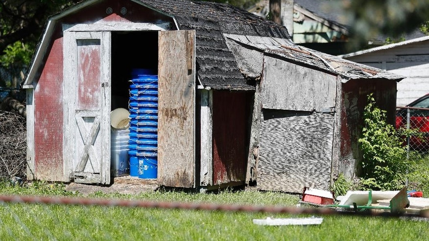 A shed stands in a backyard where police say a man with mental health problems kidnapped a neighbor and kept her trapped in a small grave-like pit in the shed Wednesday, April 26, 2017, in Blanchester. Ohio. Police in Blanchester, about 40 miles northeast of Cincinnati, said the owner of the shed, Dennis Dunn, was arrested on Wednesday. (AP Photo/John Minchillo)