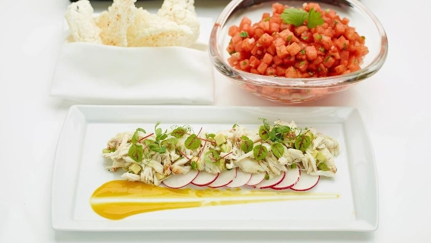 This April 24, 2017 photo provided by The Culinary Institute of America shows an avocado and crab salad garnished with sliced radish and citrus-mango sauce, foreground, a chilled watermelon salad, right, and deep fried rice crisps, left, in Hyde Park, N.Y. This dish is from a recipe by the CIA. (Phil Mansfield/The Culinary Institute of America via AP)