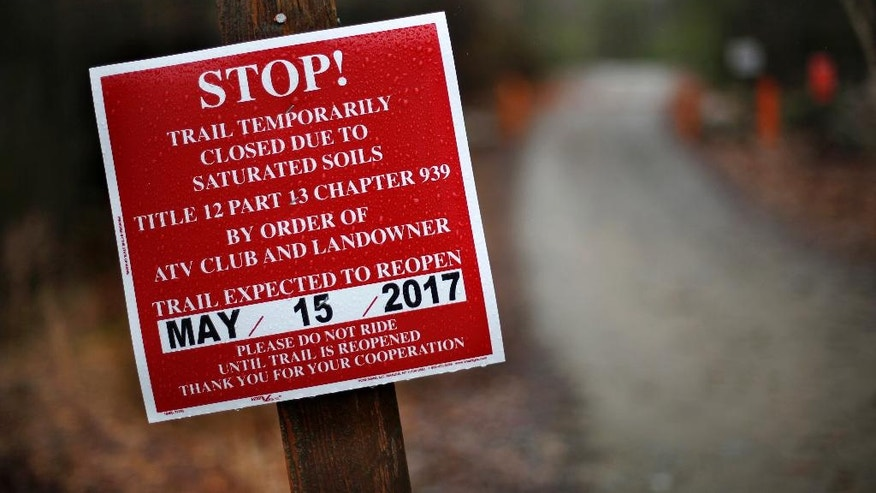 A sign warns of a closure to an all-terrain-vehicle trail at Androscoggin Riverside State Park in Turner, Maine, Wednesday, April 27, 2017. Soils saturated with snowmelt and rainwater has forced the closure of many off-road trails. (AP Photo/Robert F. Bukaty)