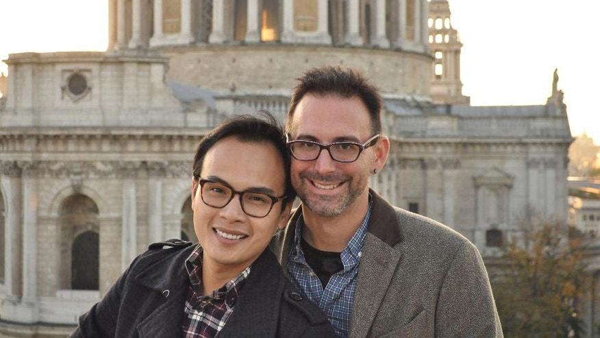 ADVANCE FOR MONDAY MAY 1 AND THEREAFTER - This 2015 photo provided by Kevin Ma shows Bobby Duong, left, and Christopher Koontz in front of St. Paul's Cathedral in London. The overall number of U.S. adoptions has dropped significantly in recent years, straining the viability of many adoption agencies and drawing some into conduct that authorities describe as unethical or worse. Would-be adoptive parents confront the specter of long waiting times and high fees. And many face pressure, as Duong and Kooontz did,  to spend lavishly on self-promotional advertising if they want to compete for a chance to adopt an infant. (Kevin Ma via AP)