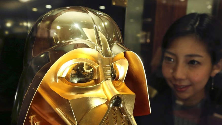 Tokyo gold jeweler Ginza Tanaka employee Momoko Marutani looks at the gold mask of Darth Vader at the jewelry shop in Tokyo, Monday, May 1, 2017. The life-size mask of Star Wars villain Darth Vader will be up for sale for a hefty price of 154 million yen ($1.38 million). The 24-karat mask was created by the gold jeweler to mark the 40th anniversary since the release of the first Star Wars film. (AP Photo/Koji Sasahara)