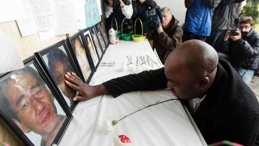 FILE - In this April 10, 2012 file photo, Efanye Chibuko touches a photo of his wife Doris Chibuko, a victim of a shooting at the university, during a memorial service at Oikos University in Oakland, Calif. A disgruntled former nursing student pleaded no contest Tuesday, May 2, 2017, to fatally shooting seven people at the Northern California vocational college and will spend the rest if his life in prison. One Goh also pleaded no contest Tuesday to injuring three others during his 2012 rampage at Oikos University. The 48-year-old was found mentally competent to stand trial last week after receiving five years of treatment for paranoid schizophrenia in a state hospital. (AP Photo/Marcio Jose Sanchez, File)