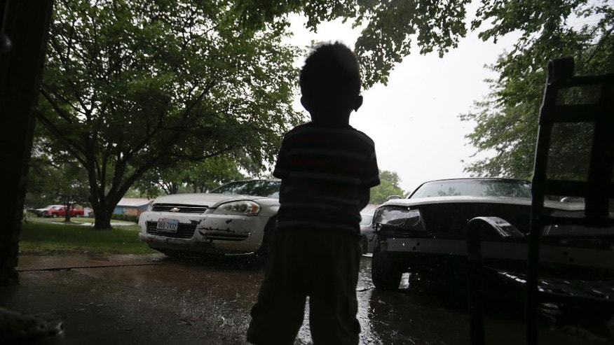 Aaiden Thomas, 2, looks out from great-grandfather's garage as the rain falls in Balch Springs, Texas, Wednesday, May 3, 2017. As the family of the black teenager slain by a white police officer calls for an indictment and more investigation, the Dallas suburb where he died faces some of the same issues with race as Ferguson, Cleveland, and other cities that have experienced high-profile police shootings of African-Americans. (AP Photo/LM Otero)