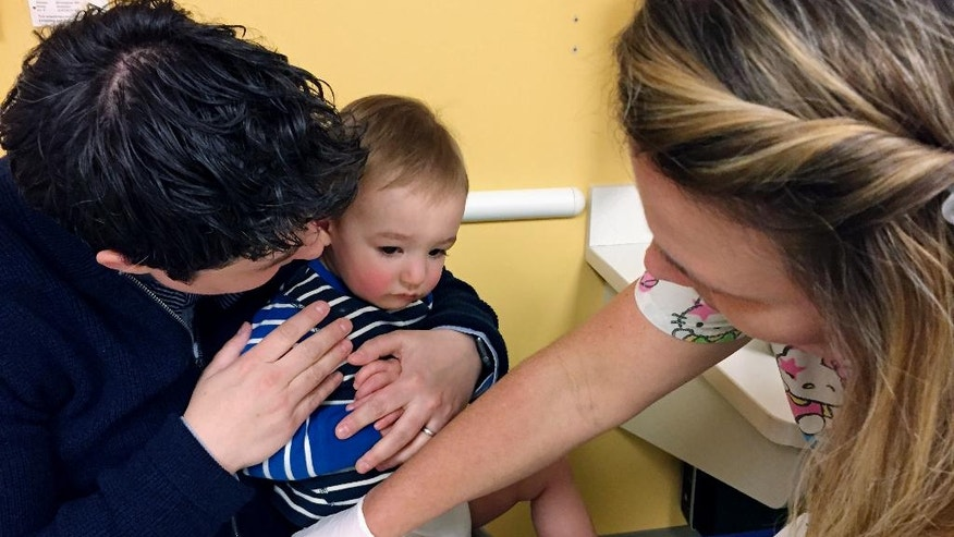 In this Tuesday, May 2, 2017, photo, 15-month-old August Goepferd received the measles, mumps and rubella booster shot at a clinic at Children's Minnesota in Minneapolis. August sat on the lap of his mom, Dr. Angela Geopferd, as registered nurse Kim Flaata administered the shot. A measles outbreak in Minnesota has sickened more than 30 children, mostly in the state's large Somali community, which has a low immunization rate. Health officials are trying to control the disease's spread by urging immunizations for the unvaccinated, as well as an accelerated booster shot schedule for children who may be at risk. (AP Photo/Amy Forliti)