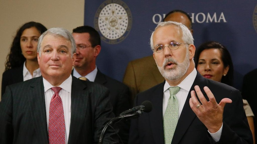 FILE - In this Tuesday, April 25, 2017, file photo, former Oklahoma Gov. Brad Henry, right, gestures as he answers a question during a news conference in Oklahoma City. Henry, one of the co-chairs of the Oklahoma Death Penalty Review Commission, announced the findings of a report that says the state should extend its moratorium on capital punishment. At left is Andy Lester, also a co-chair. (AP Photo/Sue Ogrocki, File)
