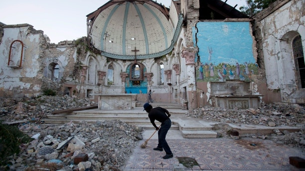 A man sweeps an exposed tiled area of the earthquake-damaged Santa Ana Catholic church, where he now lives, in Port-au-Prince, Haiti, Saturday, Jan. 12, 2013. Haitians recalled Saturday the tens of thousands of people who lost their lives in the devastating earthquake three years ago. Most of the rubble created by the quake has since been carted away but more than 350,000 people still live in displacement camps. (AP Photo/Dieu Nalio Chery)