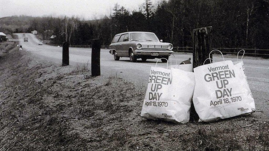 In this April 18, 1970 photo provided by Green Up Vermont, a motorist passes bags of trash gathered from along the roadway during the first Vermont Green Up Day. This year's statewide Green Up Day will be Saturday, May 6, 2017, when tens of thousands of volunteers will spread out across the state to again pick up trash. (Green Up Vermont via AP)