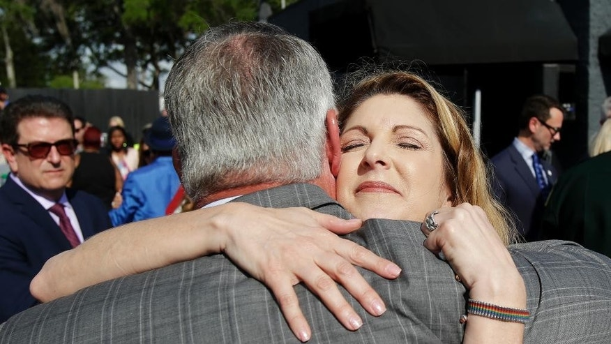 Pulse nightclub owner Barbara Poma, right, embraces Orlando mayor Buddy Dyer after a news conference announcing plans for a memorial at the site, Thursday, May 4, 2017, in Orlando, Fla. Poma said the site will become a memorial and a museum to honor the 49 people who were killed and the dozens more who were injured during the worst mass shooting in modern U.S. history. (AP Photo/John Raoux)