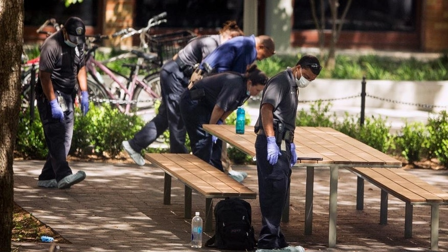 FILE - In this May 1, 2017, file photo, officials investigate after a fatal stabbing attack at the University of Texas campus in Austin, Texas. An arrest affidavit said the University of Texas student accused of stabbing multiple students, one fatally, told police he didn't remember attacking anyone. Kendrex J. White, who authorities have said suffered from mental health troubles, was charged with murder in Monday's campus attack. He remained in jail Thursday, May 4, 2017, on $1 million bond. (Jay Janner/Austin American-Statesman via AP, File)