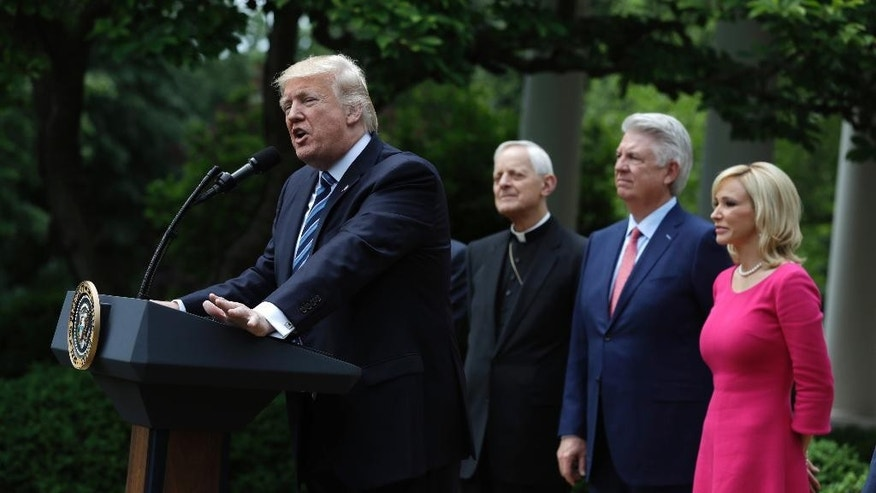 President Donald Trump speaks in the Rose Garden of the White House in Washington, Thursday, May 4, 2017, before signing an executive order aimed at easing an IRS rule limiting political activity for churches. From second from left are, Cardinal Donald Wuerl is the Archbishop of Washington, Pastor Jack Graham, and Paula White, senior pastor of New Destiny Christian Center in Apopka, Fla.  (AP Photo/Evan Vucci)
