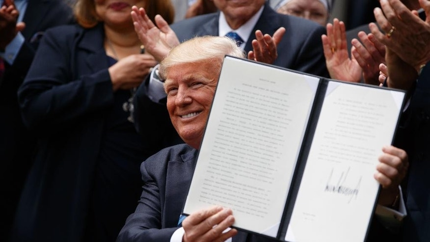 President Donald Trump holds up a signed executive order aimed at easing an IRS rule limiting political activity for churches, Thursday, May 4, 2017, in the Rose Garden of the White House in Washington. (AP Photo/Evan Vucci)