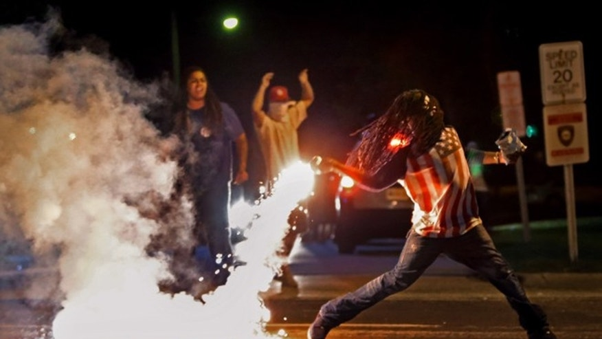 This iconic photo showed Edward Crawford returning a tear gas canister fired by police trying to disperse protesters in Ferguson, Missouri, April 20, 2015. (Robert Cohen/St. Louis Post-Dispatch via AP)
