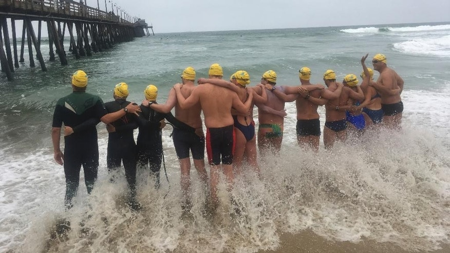 Athletes from six countries join arms before swimming off from Imperial Beach, Calif., to Mexico, in what they say is a show of solidarity with immigrants on Friday, May 5, 2017. The swimmers from the United States, Mexico, Israel, New Zealand and South Africa were escorted by a Mexican Navy ship as they reached a beach in Tijuana, a short distance from a border fence that juts into the Pacific Ocean. (AP Photo/Elliot Spagat)