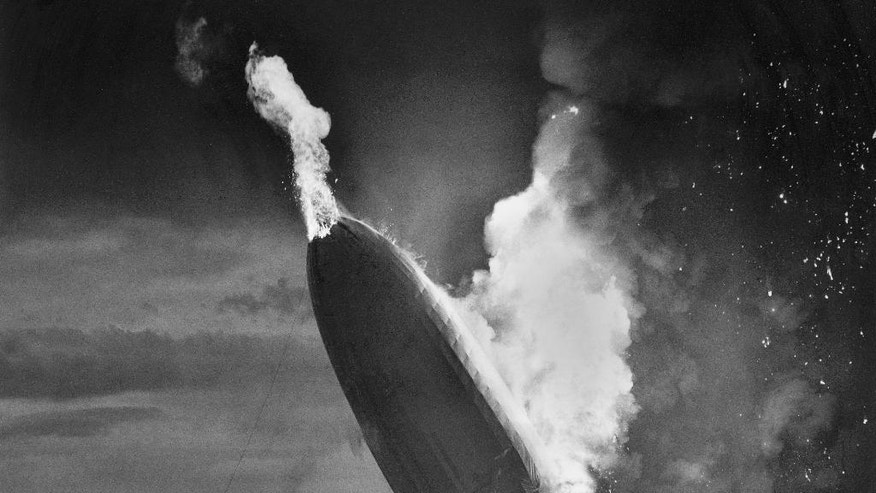 "FILE - In this May 6, 1937 file photo, the German dirigible Hindenburg crashes to earth in flames after exploding at the U.S. Naval Station in Lakehurst, N.J. Only one person is left of the 62 passengers and crew who survived when the Hindenburg burst into flames 80 years ago Saturday, May 6, 2017. Werner Doehner was 8 years old when he boarded the zeppelin with his parents and older siblings after their vacation to Germany in 1937. The 88-year-old now living in Parachute, Colo., tells The Associated Press that the airship pitched as it tried to land in New Jersey and that ""suddenly the air was on fire."" (AP Photo/Murray Becker, File)"