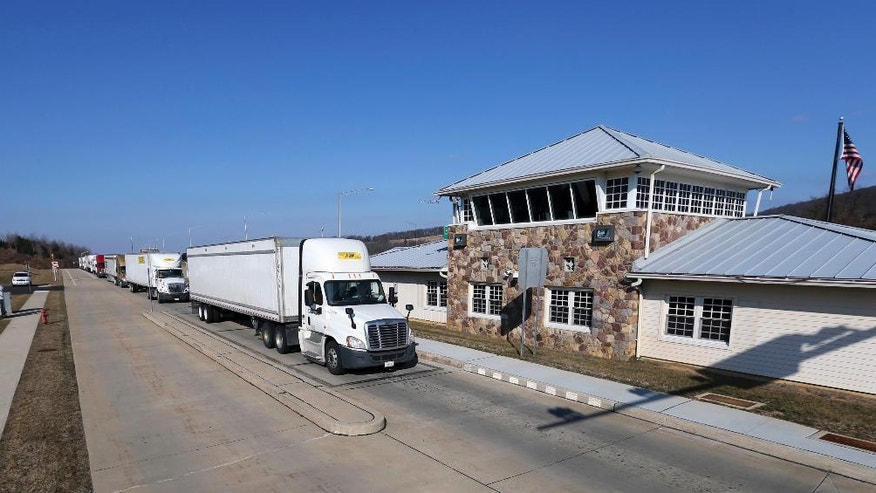FILE – In this Feb. 6, 2017, file photo, trucks line up to pass through the Greenwich truck weigh station on Interstate 78 in Greenwich Township, N.J. Truck driver Oscar Franco, of Chula Vista, Calif., was sentenced Friday, May 5, 2017, to 10 years in prison for first-degree possession of heroin with intent to distribute, and truck driver Henry A. Cruz Ventura, of Los Angeles, pleaded guilty Friday, May 5, 2017, to the same charge, according to New Jersey Attorney General Christopher Porrino. New Jersey State Police arrested Franco and Ventura in August 2016, after seizing drugs during inspections at the weigh station in Greenwich Township, N.J. (AP Photo/Mel Evans, File)