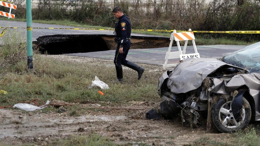 FILE - In this Monday, Dec. 5, 2016, file photo, a San Antonio police officer walks past a sinkhole and a vehicle that was pulled from it, in San Antonio. Sudden-appearing caverns are happening in places where they once were rare. Unlike most earthen collapses in the past, the new cave-ins are being caused by crumbling water and sewer pipes rather than unstable geology. (AP Photo/Eric Gay, File)