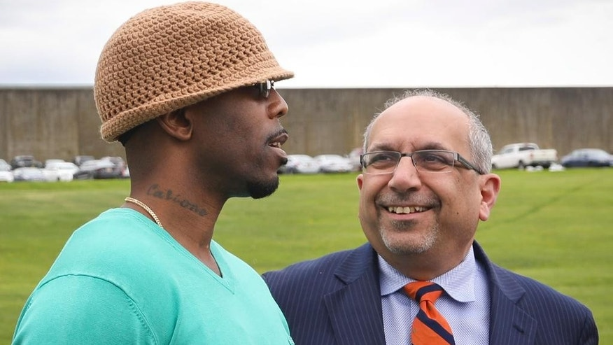 Calvin Buari, left, talks with his lawyer Oscar Michelen following his release from Green Haven correctional facility, shown in background, Monday, May 8, 2017, in Stormville, N.Y. Buari, who spent 22 years in prison for a double killing he said he didn't do, was freed after his conviction was overturned.(AP Photo/Bebeto Matthews)